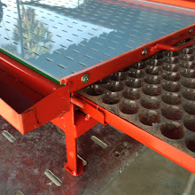 Photo: A device used to quickly drop a single grain into plastic trays for germinating rice seeds as plugs that can be used in dart transplanting (Thai Weekend Farmer's Network).  [Photo by Devon Jenkins, Thailand, 2014]