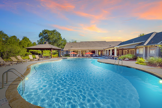 Brigham Woods' swimming pool with lounge chairs and poolside grilling pavilion at dusk
