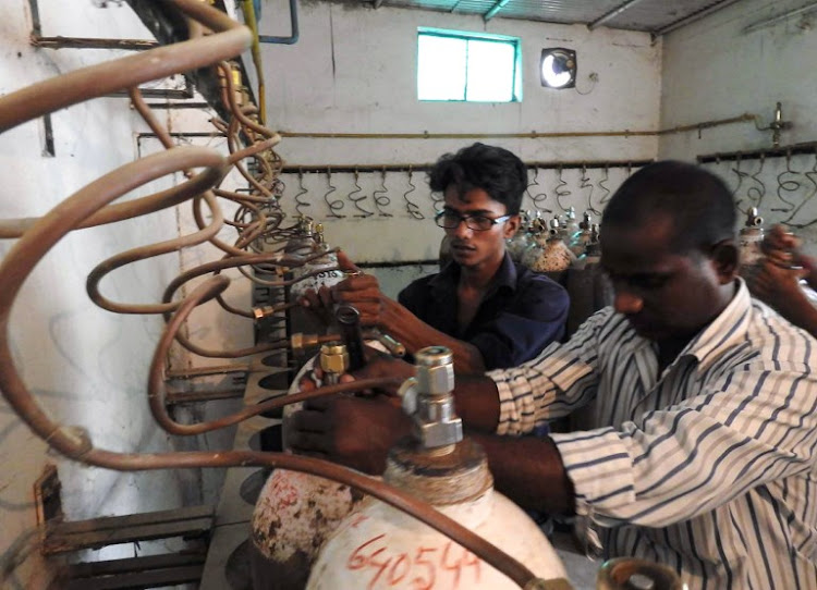 Indian workers examine oxygen cylinders at the Baba Raghav Das Hospital in Gorakhpur, in the northern Indian state of Uttar Pradesh, on August 12, 2017.