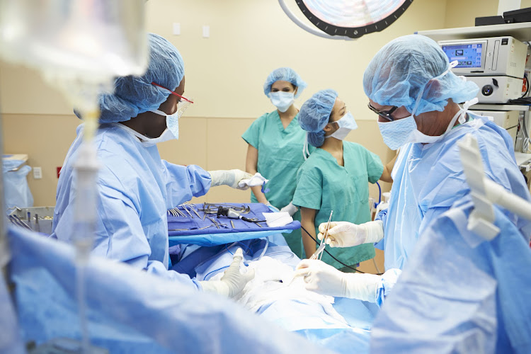 Surgical team working in operating theatre.