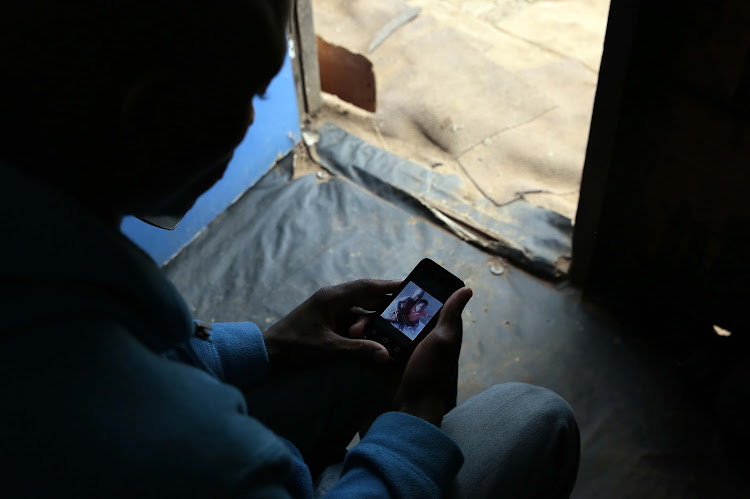 The father of a 3-year-old boy whose body was found at a local dumpsite after he was allegedly tormented and killed by children in Primrose, Germiston, looks at a picture of his son on his cellphone.