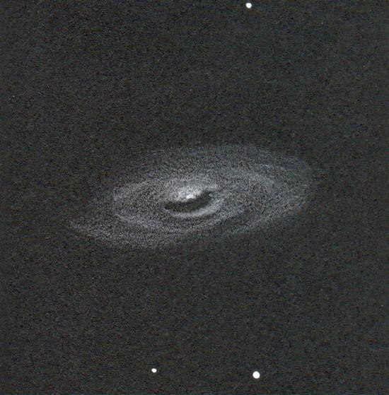 Photo: M64, l'œil noir, au T406 à 195X. En plus de la fameuse virgule sombre, des morceaux de spires apparaissent. Dessin en blanc sur papier noir, scan de mauvaise qualité.