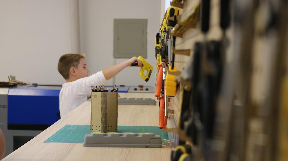 A imagem mostra um adolescente em frente a uma bancada de ferramentas.