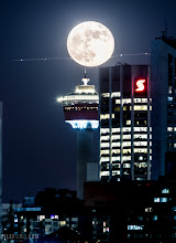 "Photo: Supermoon, Airplane and Calgary Tower in one Calgary, Alberta, Canada  I really wanted a photo of the supermoon against something that was iconically Calgary. At the same time I didn't want to photoshop the moon to make it look bigger. In order to show a large moon I had to use a telephoto lens and be somewhat far from the tower itself. This meant mapping the path of the moon ahead of time and knowing where I had to stand to get the Calgary tower visible. After a few calculations I knew that I had to be at the Jubilee auditorium, a place I've always gone to and had a fantastic time watching Alberta Ballet or other fantastic shows.  One other problem with shooting such a bright object is that the camera can't capture the comparatively dim lights of the towers and the bright moon at the same time. This required that I take two photos at different exposure levels and mash them together to get the combined details of the moon's beautiful craters and the city's vibrant textures. I had the lucky bonus of an airplane flying in front of the moon while I took the shot, creating a cool streak across the sky.  I have to stress that the the size or shape of the moon has not been manipulated, the only ""photoshopping"" in this photo is the combining of the two exposures, the large size of the moon is magnified just as much as the tower is by using my 400mm lens on a canon 7D.  Exposure 1 for the city: 4s f/8.0 ISO200 400mm (Brighter) Exposure 2 for the moon 1s f/8.0 ISO100 400mm (Darker)  For #satudaynightlight curated by +Dirk Heindoerfer"