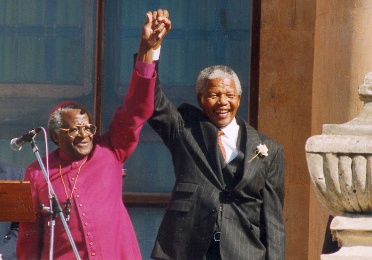 Nelson Mandela, right, and Desmond Tutu, left, raise clasped hands in celebration at the African National Congress election victory, in April 1994. Picture: SUNDAY TIMES