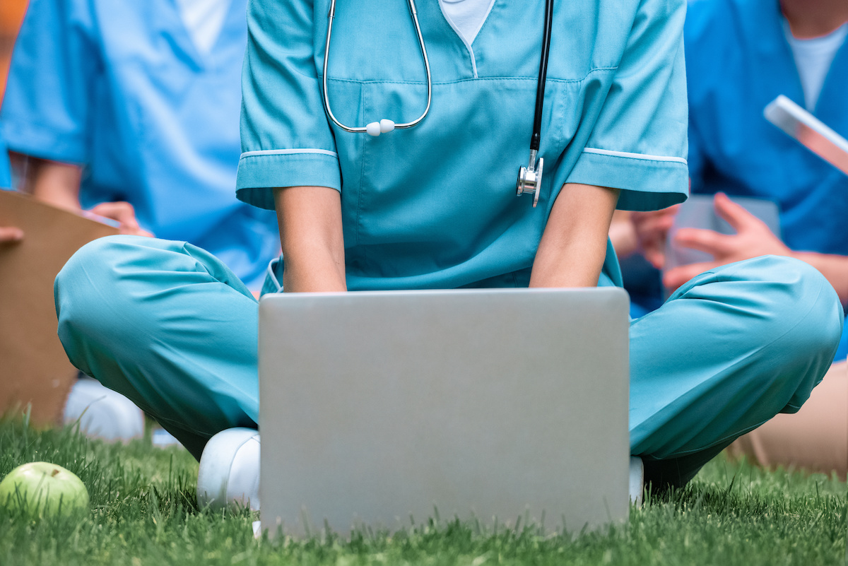 BSN Programs: medical student studying with laptop on green grass