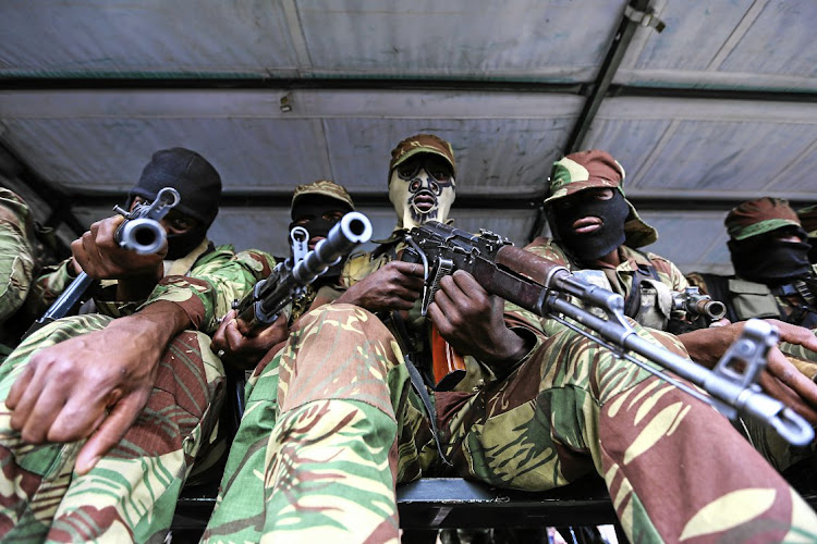 Zimbabwe military troops stand guard during November 2017 negotiations to remove Robert Mugabe as the country's president. It emerged this week that military officials warned that a fight-back by Mugabe would have resulted in bloodshed.