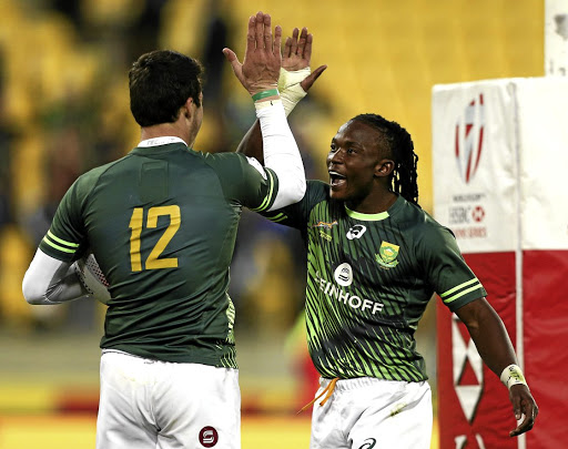 High five for high seven: Ruhan Nel, left, and Seabelo Senatla celebrate the Blitzboks Sevens Cup final  victory over champions Fiji. Picture: GETTY IMAGES/HAGEN HOPKINS