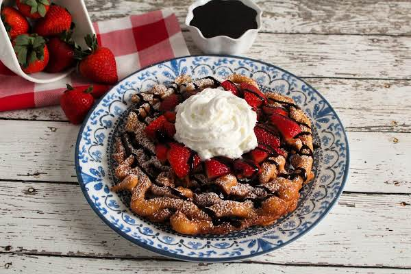 Funnel Cakes Topped With Powdered Sugar, Chocolate Sauce, Strawberries, And Whipped Cream.