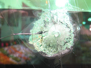 Photo: Bullet hole in shop window glass, Nashville, seen from the outside (i.e. the ejected region is on the far side of the glass while I am looking in from the outside).