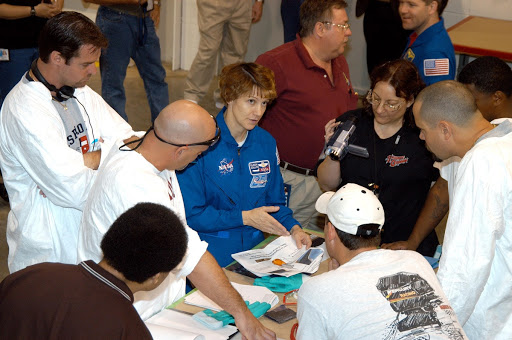STS-114 Commander Eileen Collins center asks the thermal protection system technicians questions about work they are doing.