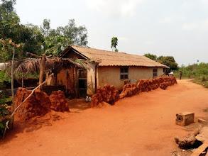 Photo: les constructions se multiplient tout autour, mais les murs en terre de barre ne résistent pas aux fortes pluies