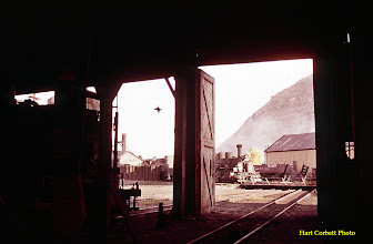 Photo: 074-21.  View out from inside the old roundhouse.  The engine in the dark at left is K-36 #481; the engine approaching the turntable is K-28 #473.  The number of the engine by the sand house is unknown.  7/25/60.