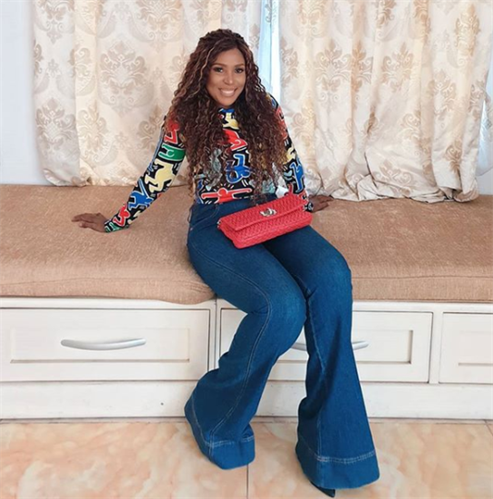 Nigerian blogger Linda Ikeji in jeans and printed top sitting in a window seat - Top 25 Social Media Influencers Making Impacts in Nigeria Today