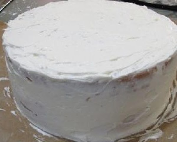 Once your cake has cooled, you'll want to crumb coat your cake. To insure...