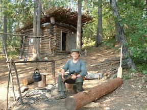 Ich posiere mit Wolodjas Gewehr vor der Jagdhütte.