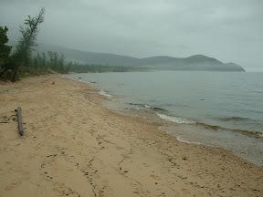 Immer wieder schütten Schauer aus den tiefziehende Wolken. Der See ist unwirtlich und die Wanderung zum Vorgebirge am Ende der Bucht erschien keinem mehr erstrebenswert.
