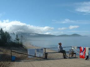 Am Anleger: Tanja genießt die Morgenstimmung während der Wache und hält gleichzeitig Ausschau nach einem Boot, welches uns zurück zur Ajaja-Bucht bringen könnte. Im Hintergrund Erkennt man Nebelschwaden und tiefziehende Wolkenreste.