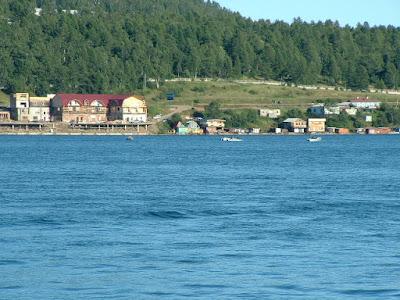 Der Schamanenstein (im Wasser vor dem großen Gebäude) ist kaum zu erkennen. Der Legende nach schleuderte der Vater Baikal diesen Felsbrocken seiner Tochter Angara hinterher, als diese ihn für den Recken Jenissej verließ.
