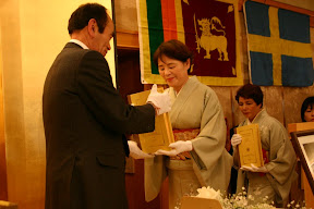 Dhamma Society Chancellor receiving the Roman-script Tipitaka from Japanese Patron.