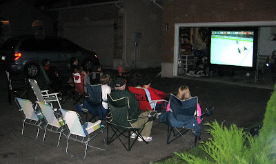 TV in garage with lawn chairs in the driveway