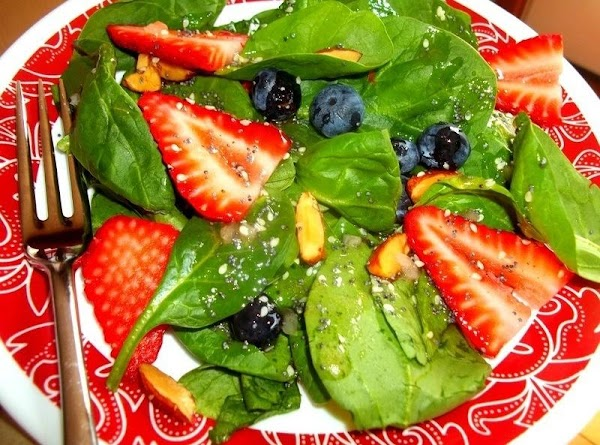In a large serving bowl, combine the spinach, strawberries, blueberries and almonds. Toss gently...