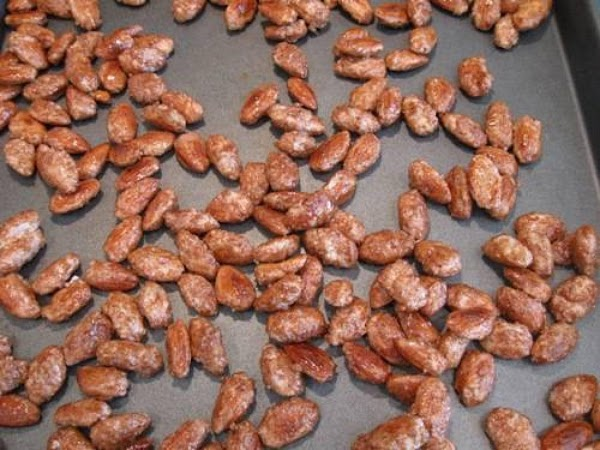 Spread the almonds on a cookie sheet. They are very hot, so only use...