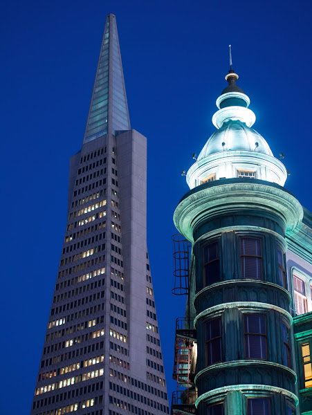 Photo: Two Towers, San Francisco  Columbus Avenue has long been one of my favourite streets in San Francisco. I love the way it defiantly cuts diagonally across the grid, connecting the tacky tourism of Fisherman's Wharf with the cafes and restaurants of North Beach before terminating at the Financial District, satisfyingly punctuated by the pointed tower of the Transamerica Pyramid.  The Pyramid has of course become an icon of San Francisco, appearing in countless logos and posters; it's funny to remember that, like many classic buildings, it was less than popular when first proposed. But today most of us love the Pyramid and its constant presence on the horizon when walking up Columbus Avenue away from Fisherman's Wharf.  Like all classic buildings, the Transamerica Pyramid presents a broad selection of smart views whether face-on, or tantalizing glimpses between other blocks. +Thomas Hawk  generously shared a great viewing location on Montgomery Street during a recent North Beach photowalk; you can see my take of that earlier in my stream. One of my other favourite views though captures not one, but two classic Columbus Avenue towers: the Transamerica Pyramid and the Sentinel Building.  The green Sentinel Building is on the corner of Columbus Avenue and Kearney Street and is the home of Zoetrope, the production company of Francis Ford Coppola. The whole area is steeped in modern history. Just up the road is City Lights Bookstore and Vesuvio, haunts of the original beat poets, and popular legend has it, that Coppola penned The Godfather in a nearby café.  San Francisco locals can confirm the history, but what I can tell you is the Sentinel Building and Transamerica Pyramid line-up beautifully if you stop on the corner of Columbus and Kearney and step out a meter or so onto Columbus itself. By shuffling around and crouching down you're able to pretty much position both towers as you wish. I'd like to take the credit for the composition, but of course many others have been there before me. I actually first saw it on the cover of a Lonely Planet guidebook ages ago and decided I'd try and find it in person.  Over the years I've photographed the view many times, but this shot, taken just a couple of weeks ago, is one of my most successful. It was dusk and just dark enough for the building lights to look good, while retaining the twilight blue of the sky. It's much nicer than during daytime hours. You'll need a short telephoto lens for a similar composition, and I had a great one in my bag: the Olympus 45mm f1.8, fitted onto my Panasonic GX1 Micro Four Thirds body where it delivers a 90mm equivalent field of view.  Problem was, it was getting dark. Even with the lens fully opened at f1.8, the GX1 was metering shutter speeds around 1/10 at 200 ISO. Without stabilization or a tripod, I had no choice but to gradually bump up the sensitivity until I could grab a sharp image. I ended up at 800 ISO and a shutter speed of 1/40, which I managed to handhold while leaning against a post. Ideally I'd have used a tripod and reduced the ISO for a cleaner image, while also closing the aperture to its sharpness sweetspot at around f4-5.6, but to be honest the image holds up reasonably well under close inspection - testament to the quality of that lens. Given a tripod for steadiness, I'd also have moved a little further into the road to ensure a small gap between the buildings, although it may have made them literally look a little detached.  But you have to make do with the gear and conditions you've got, which for me was a handheld snap shortly after a delicious meal of Salt and Peppar Crab at the R&G Lounge just moments away on Kearney Street. That's another SF classic and, coupled with Columbus Avenue, yet another reason why I rarely stay away from the city for very long.