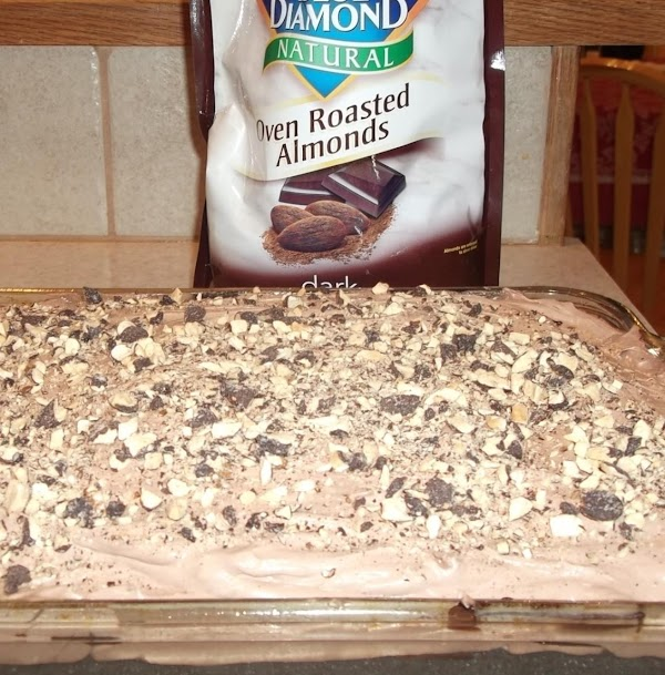 Cover the cake with the creamy pudding and top it with chopped cocoa almonds.  The almonds are amazing AND they keep the plastic wrap from sticking to the good stuff.