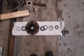 Photo: Left front hub parts removed for inspection. Order from L-R as installed on the axle. Castle nut and cotterpin missing in photo and would be on far right-hand side where the Combination Square is located. Note the far left bushing followed by a tapered roller bearing, then the wheel hub. This is different assembly order versus the right-hand hub side, as we discovered.