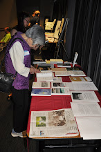 Photo: Fumiko Kimura checks out the books on display on our book table. In the foreground is a front-page Seattle Times newspaper story on the Seward Park Torii project, including the top three winners in a haiku contest they ran (I served as judge).