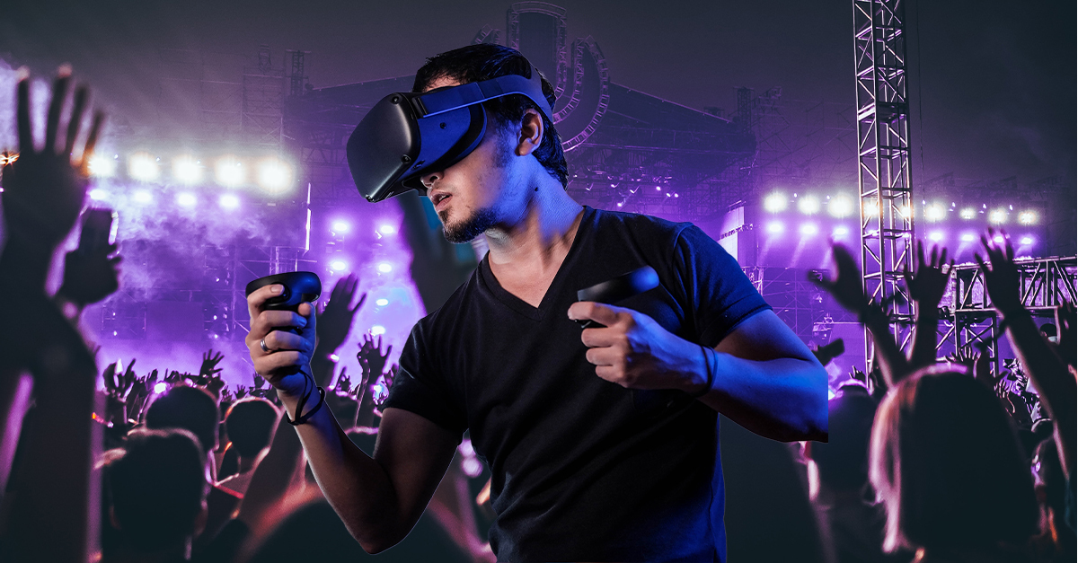 Man wearing a VR headset and holding a controller among a crowd of people at Glastonbury.