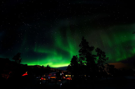 The northern lights dance over a hillside village in Norway as seen from a cruise ship on the coast.