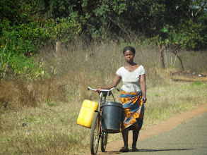 Photo: a woman going to get water- most likely at the closest school, where the community water pumps tend to be