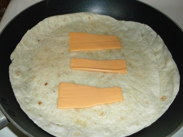 Uncover tortillas; place torn american cheese slice on each (sprinkle with chives, if desired.)