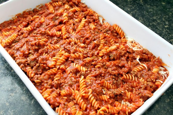 A layer of cheese added to the ground beef and pasta mixture in a baking dish.
