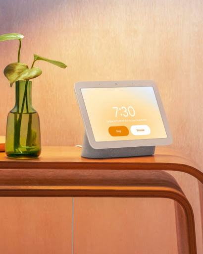 Nest Hub is on top of a bedroom counter. The screen displays information that is backlit by a gentle orange glow.