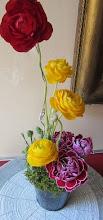 Photo: Composition printanière piquée dans de la mousse floral fleurs utilisées: renoncules jaune et rouge, oeillets violets  prix:12 euros contenant sceau en zinc