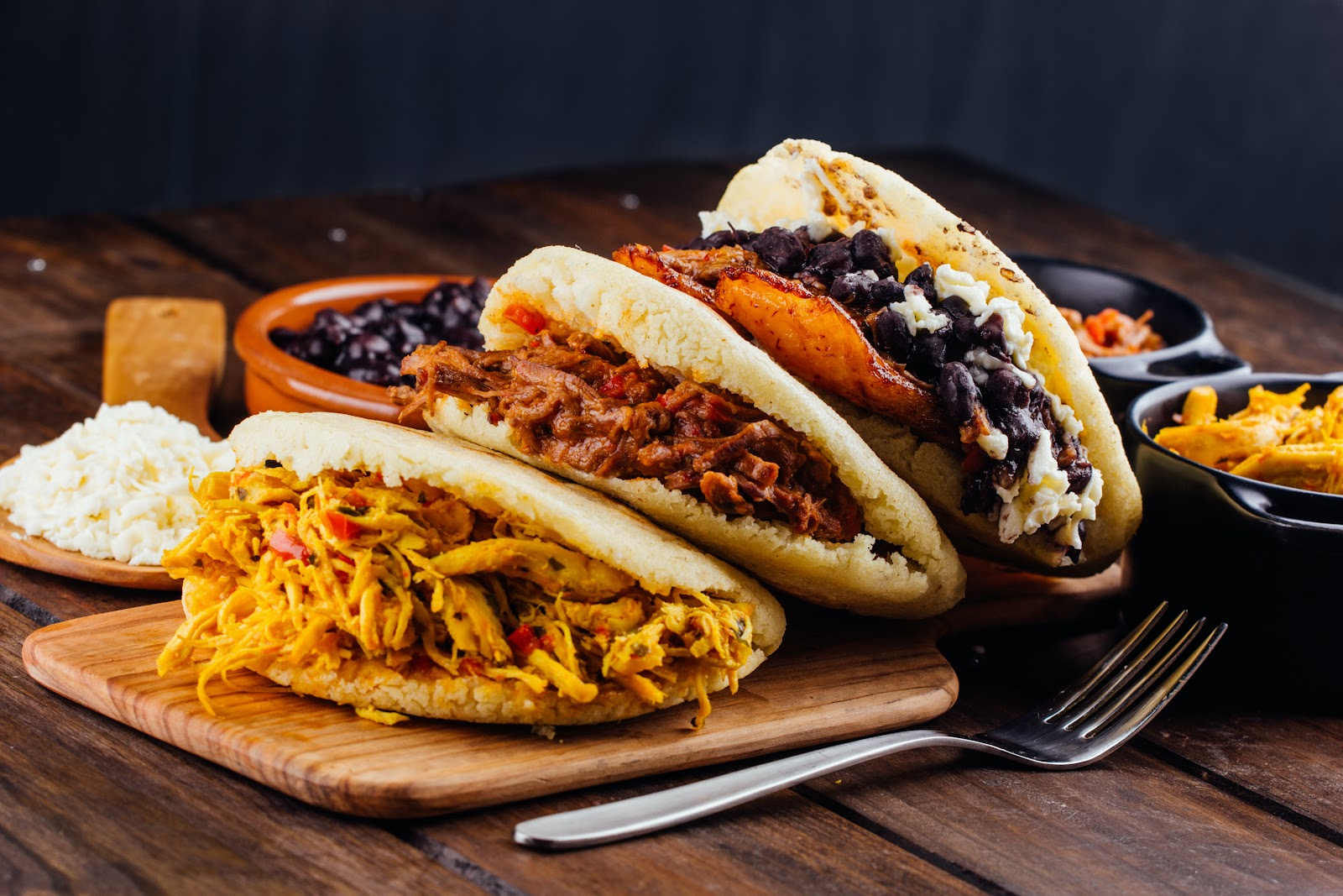 Viva Las Arepas in Las Vegas serving three arepas on a wood board with beef, beans, rice, pork, and more.