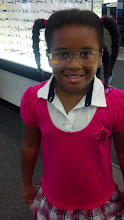 Photo: Kaleya tries on glasses as her daddy shops for a new pair