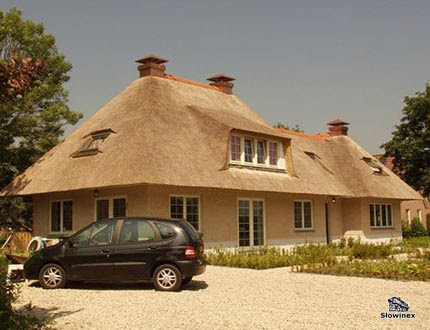 Samochód stojący przed eleganckim domem z pokryciem trzcinowym