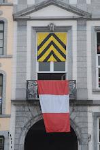 Photo: Sur une façade de la grand-place, les couleurs du chapitre de Sainte-Waudru et celles de la Ville de Mons .