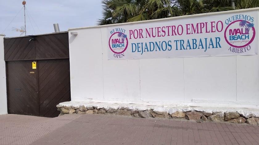 Cartel colocado por los trabajadores a la entrada del Maui, reclamando la reapertura del chiringuito.