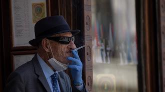 Un hombre con mascarilla y guantes fumando un cigarro en Sevilla.