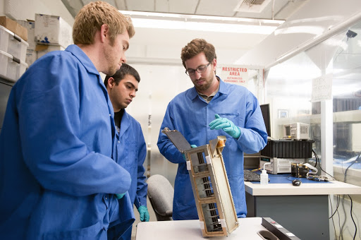 Members of the student launch team for the Polysat works through final checks in the CubeSat lab facility at California Polytechnic Institute.