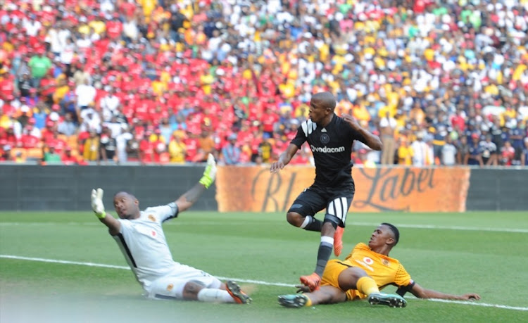 Luvuyo Memela of Orlando Pirates scoring his goal past Itumeleng Khune and Siyabonga Ngezana of Kaizer Chiefs during the Absa Premiership match between Orlando Pirates and Kaizer Chiefs at FNB Stadium on March 03, 2018 in Johannesburg.