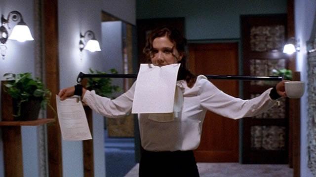 Lee Holloway wearing restraints carries a letter in her teeth in secretary 2002