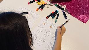 Una niña trabaja en el diseño de sus pendientes usando la plantilla de base.