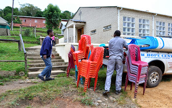 Photo: Outside of the tabernacle with the boys house in the background and the men unloading the chairs.