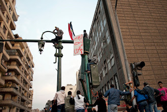 Photo: Men sit on street lamps to get a better view of the frontline action...